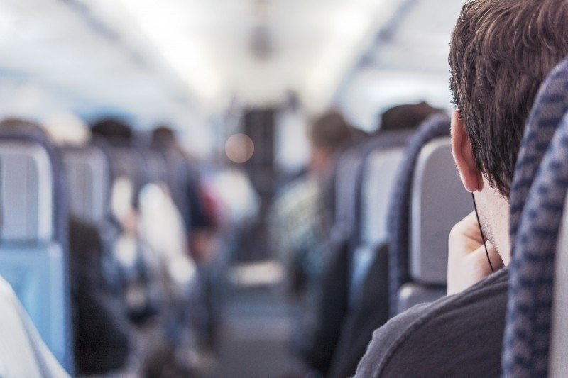 Mężczyzna ze słuchawkami na pokładzie samolotu